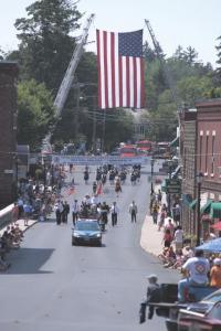 Ladder trucks support a large American Flag forming an arch for fire departments from all over Vermont to be recognized during this years state convention hosted by The AddisonCounty Firefighters Association.