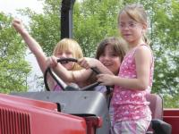 Celebrating the event, local children sit atop a tractor and dream of what they will plant!