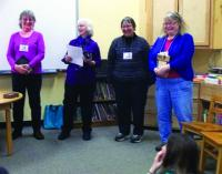 Local DAR members share a smile and some stories as they donate books to a local elementary school library.
